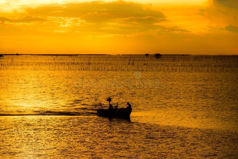 Sylwetka łódź rybacka i rybacy w morzu obraz stock