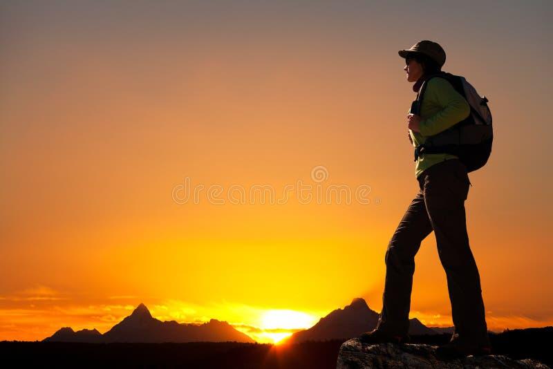 Sylwetka żeński wycieczkowicz przy zmierzchem. zdjęcie stock