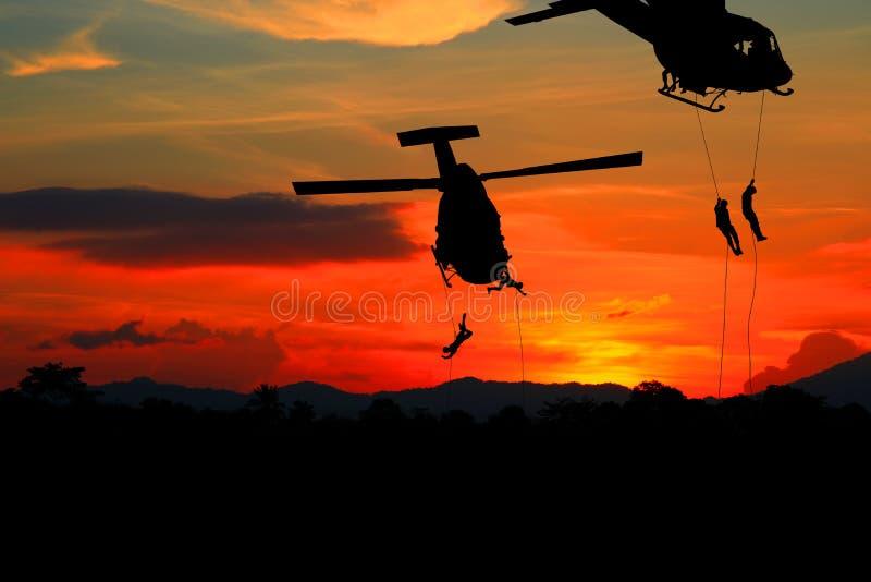 Sylwetka żołnierze rappel puszek atakować od helikopteru z zmierzchem obraz stock