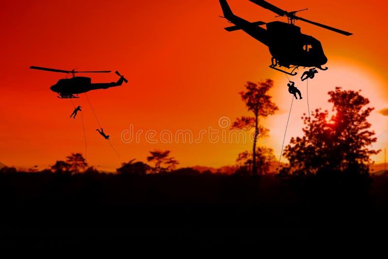 Sylwetka żołnierze rappel puszek atakować od helikopteru z zmierzchem obraz royalty free