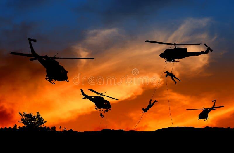 Sylwetka żołnierze rappel puszek atakować od helikopteru z zmierzchem fotografia stock