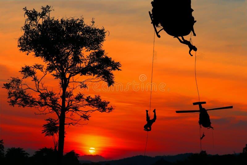 Sylwetka żołnierze rappel puszek atakować od helikopteru z zmierzchem i kopiować przestrzeń dodaje teksta pojęcia przerwy wrogość zdjęcie royalty free