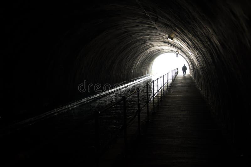 Sylwetka Appraching mężczyzna Przed Jaskrawym światłem Przy końcówką Ciemny tunel obrazy royalty free