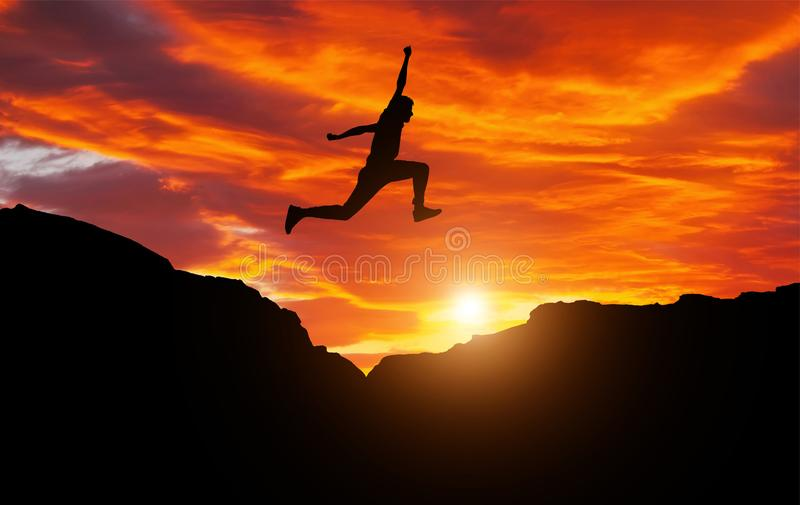 Sylwetka atleta, skacze nad skałami w terenie górskim fotografia stock