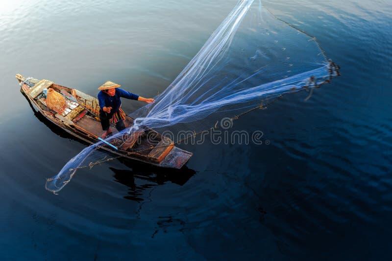 Sylwetka azjatykci rybak na drewnianym łódkowatym kastingu sieć dla catc obrazy stock