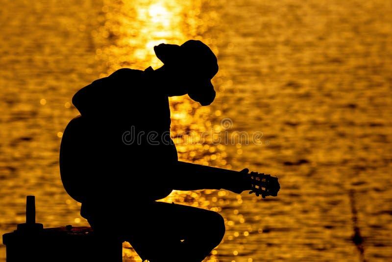 Sylwetka bawić się gitarę na rzece pod gitarzysta fotografia stock