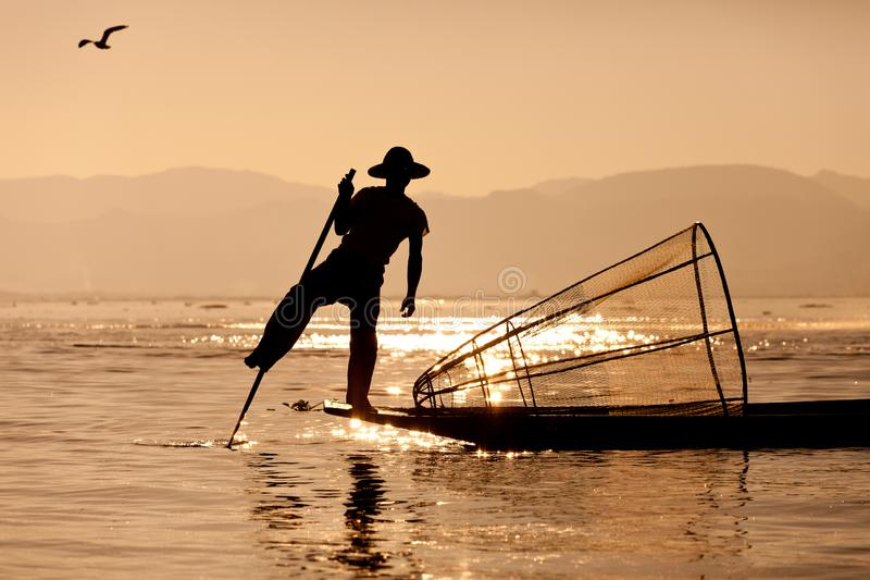 Sylwetka birmańskiego rybaka na drewnianej łodzi o zachodzie słońca Mjanmańscy rybacy na łodziach bambusowych łowiących ryby w tr zdjęcia royalty free