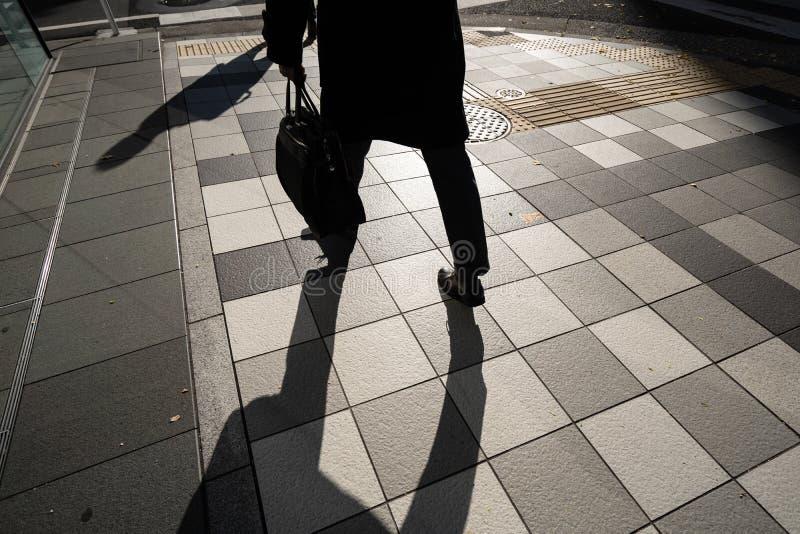 Sylwetka biznesmen, biurowy faceta mienia torby odprowadzenie pracujący w ranku w Tokio, Japonia zdjęcie royalty free