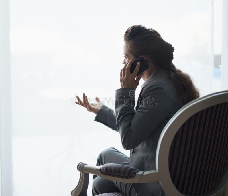 Sylwetka biznesowej kobiety opowiada telefon komórkowy zdjęcia stock