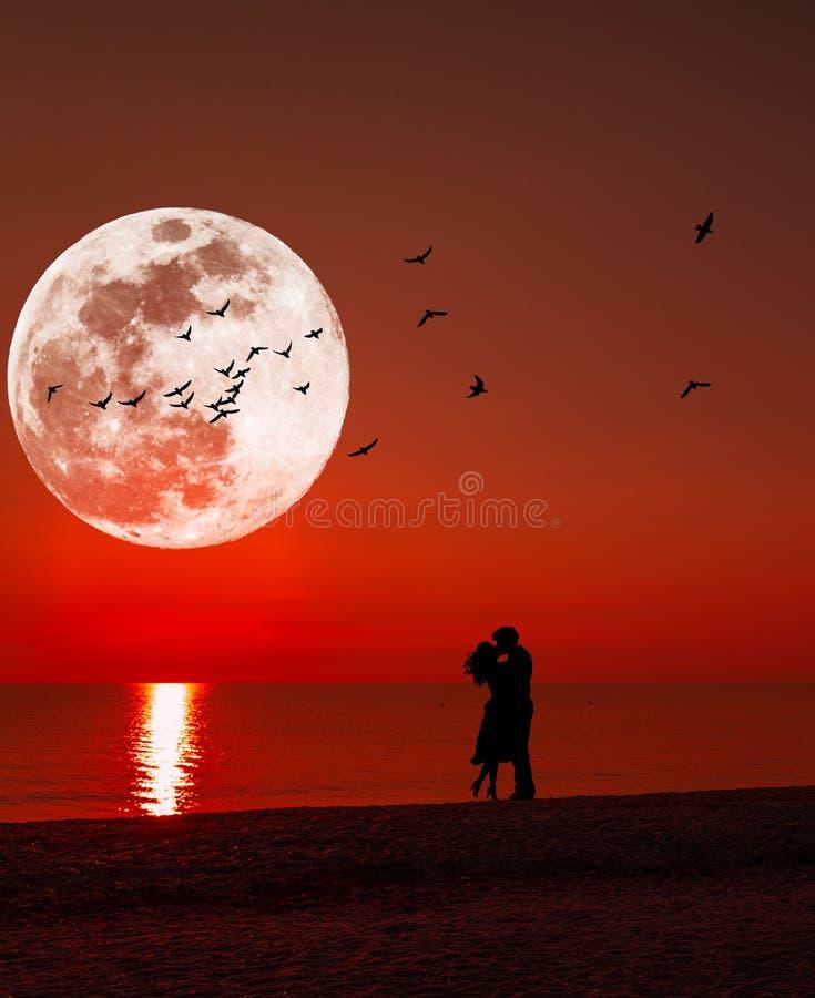Sylwetka całowanie para pod księżyc w pełni przy zmierzchem obrazy royalty free