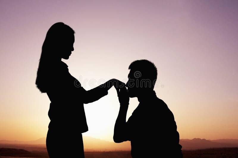 Sylwetka chłopaka całowanie i klęczenie jego dziewczyny ręka przy zmierzchem zdjęcia stock