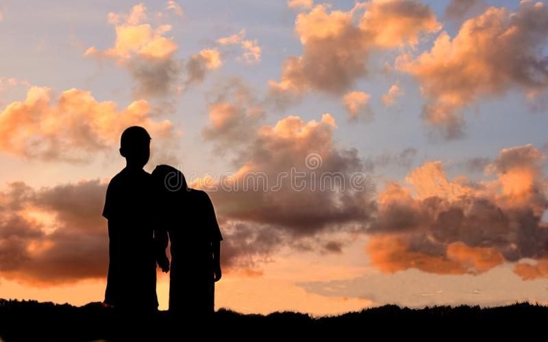 Sylwetka chłopiec i dziewczyny stojak ręka w rękę oglądać zmierzch fotografia stock