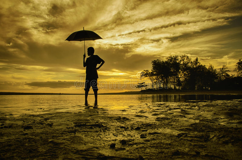 Sylwetka chłopiec spojrzenie przy plecy i pozycja podczas gdy trzymający parasol zdjęcie royalty free