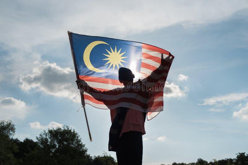 Sylwetka chłopiec trzyma malezyjską flaga świętuje Malezja dzień niepodległości obraz stock