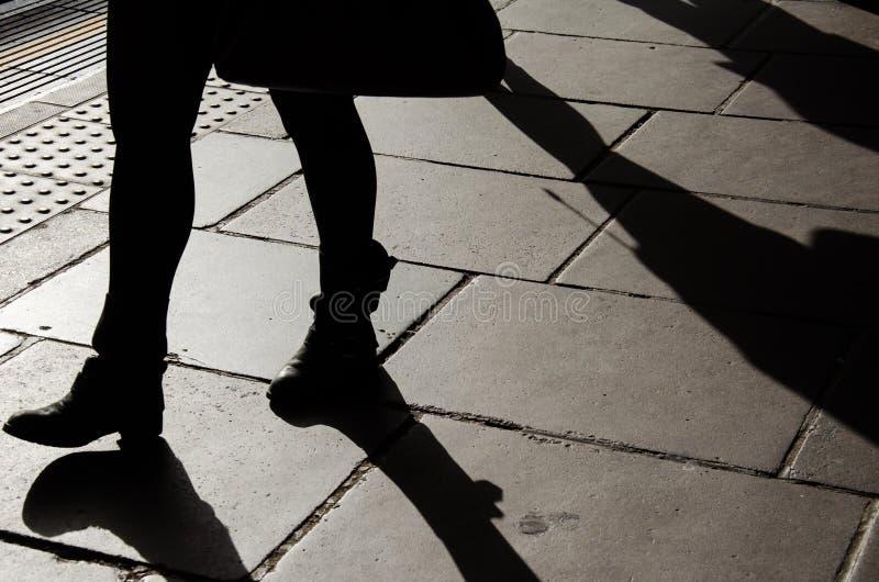 Sylwetka chodząca kobieta iść na piechotę z butami przy godziną szczytu fotografia royalty free
