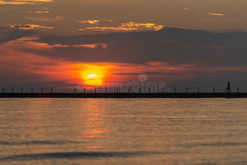 Sylwetka chodzÄ…cego mężczyzny w Pionierze przy Sunrise z odbiciem sÅ'onecznym nad jeziorem Michigan zdjęcia stock