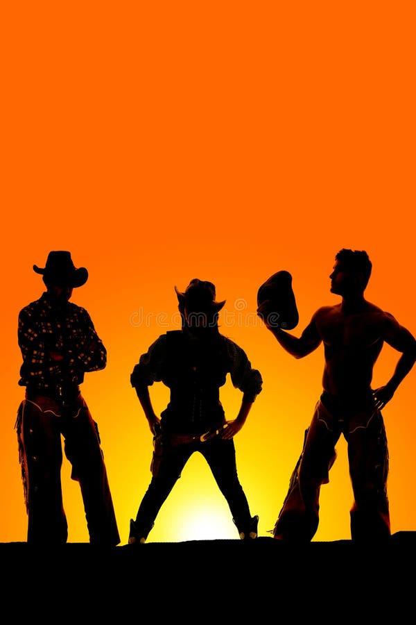 Sylwetka cowgirl prosto dalej między dwa kowbojami obraz royalty free