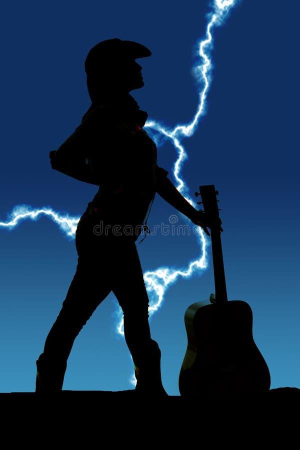 Sylwetka cowgirl z gitarą jej spojrzeniem popierać kogoś zdjęcie royalty free