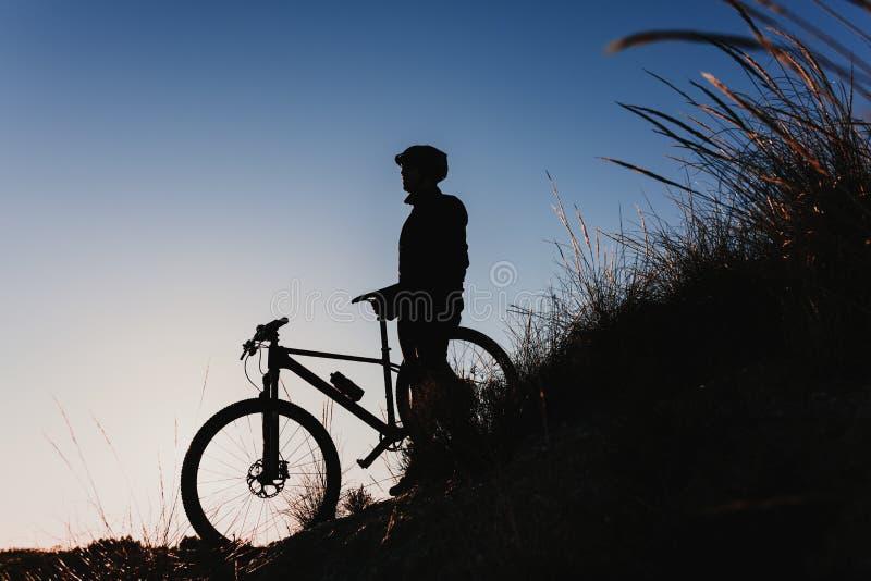 Sylwetka cyklista Jedzie roweru puszka Skalistego wzgórze przy zmierzchem Krańcowy sporta pojęcie zdjęcie stock