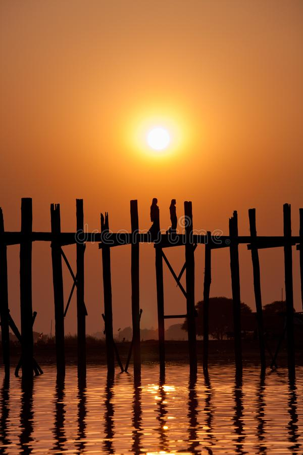 Sylwetka dwóch dziewcząt na moście U Bein w zachodzie słońca, Amarapura, region Mandalay, Myanmar. Birma. Sylwetka dwóch dzi obrazy royalty free