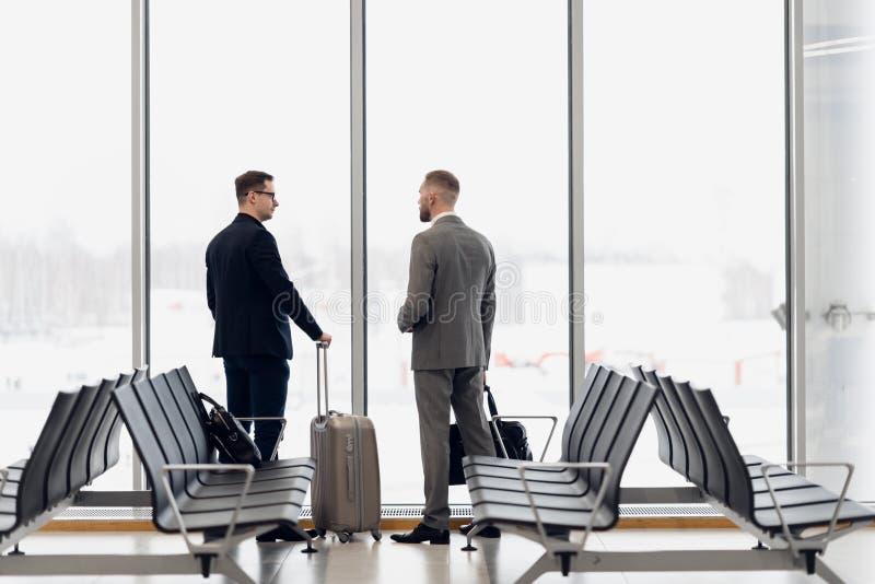 Sylwetka dwa biznesmen?w pozycja przed du?ym okno przy lotniskiem przy wating terenem blisko wyj?ciowej bramy zdjęcia stock