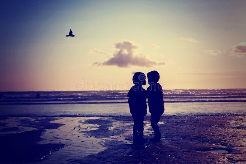 Sylwetka dwa dzieciaka, całuje na plaży zdjęcie royalty free