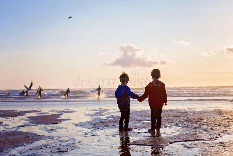 Sylwetka dwa dzieciaka, ogląda surfingowów na plaży zdjęcia royalty free