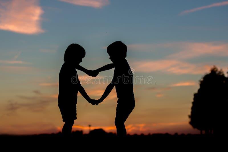 Sylwetka dwa dziecka, chłopiec bracia, robi kierowemu kształta dowcipowi fotografia stock
