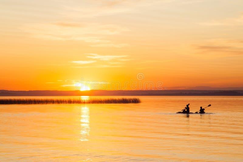Sylwetka Dwa kajakarki na jeziorze podczas zmierzchu fotografia royalty free