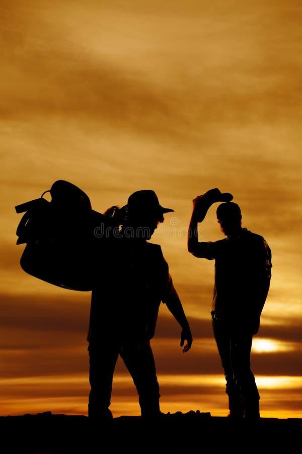 Sylwetka dwa kowboja w zmierzchu jeden chwyta comberze na shoul zdjęcia royalty free