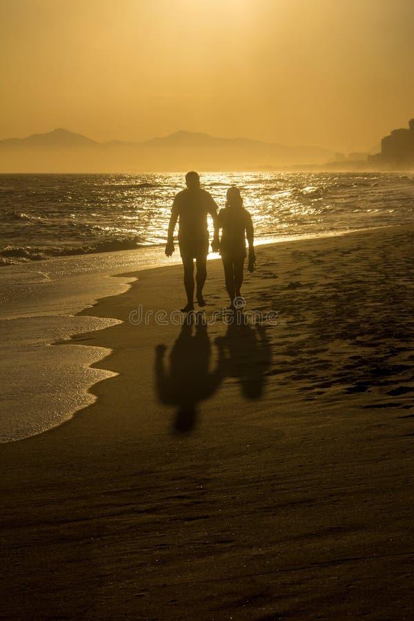 Sylwetka dwa męskiego przyjaciela chodzi wzdłuż plaży podczas su obrazy royalty free