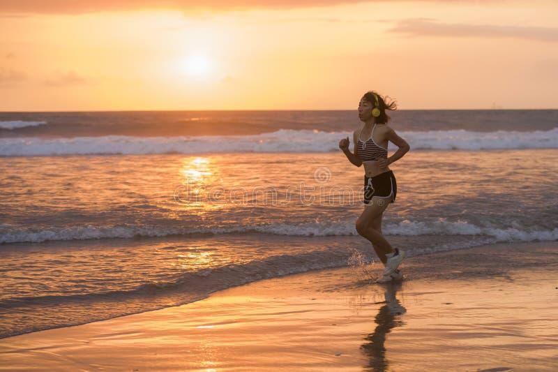 Sylwetka dysponowany i sportowy Azjatycki Chiński sporty kobieta bieg na pięknej plaży robi jogging treningowi na zmierzchu w spr zdjęcia royalty free