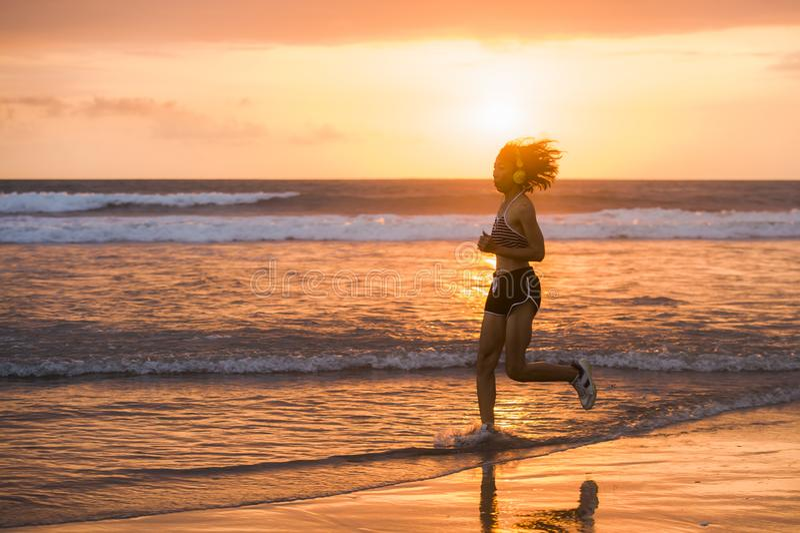 Sylwetka dysponowany i sportowy Azjatycki Chiński sporty kobieta bieg na pięknej plaży robi jogging treningowi na zmierzchu w spr obraz stock