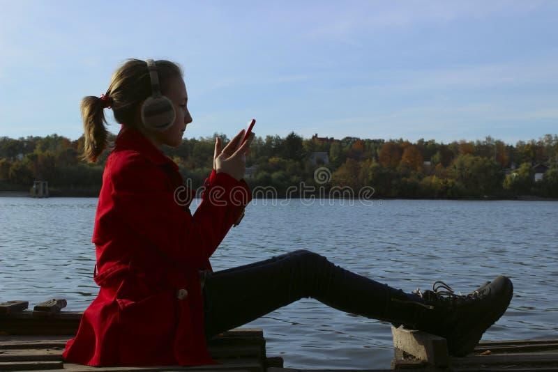 Sylwetka dziewczyna siedzi Blisko Wodnego I Używa Smartphone obraz stock