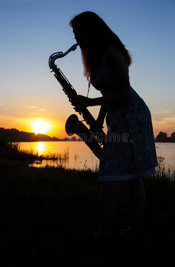 Sylwetka dziewczyna w sukni przy świtem blisko rzeki w wiosce bawić się saksofon na tle niebieskie niebo zdjęcia royalty free