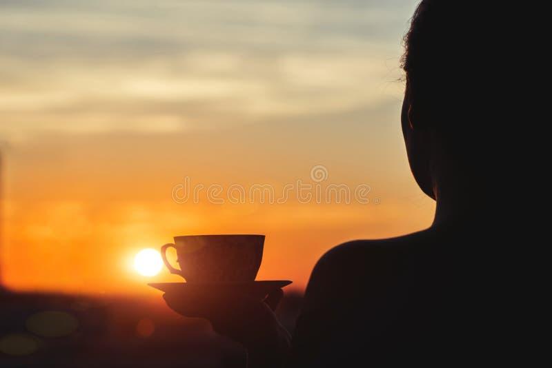 Sylwetka dziewczyna z filiżanką kawy w ranku Widok na miasteczku od above fotografia stock