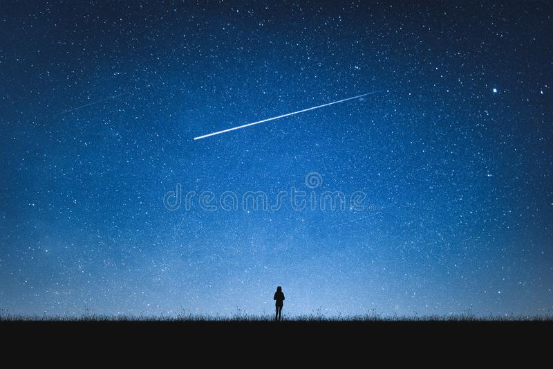 Sylwetka dziewczyny pozycja na górze i nocnym niebie z mknącą gwiazdą samotny pojęcie zdjęcia stock