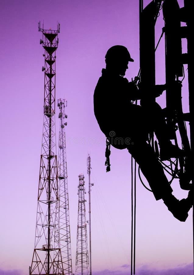 Sylwetka fachowy przemysłowy arywista w hełmie i mundurze pracuje przy wzrostem dla instaling komunikację zdjęcia stock