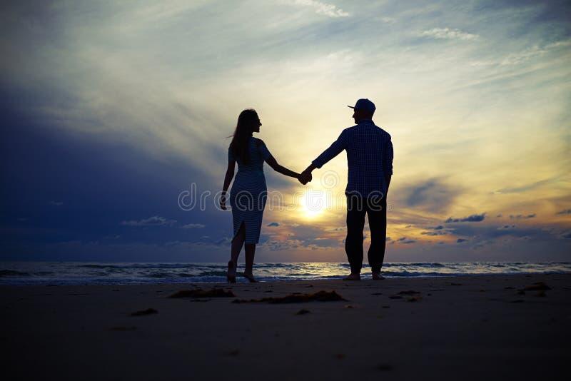 Sylwetka fascynować urocze pary mienia ręki przy uns zdjęcia royalty free