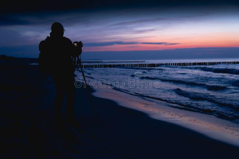 Sylwetka fotograf przy półmrokiem na opustoszałej plaży obrazy stock