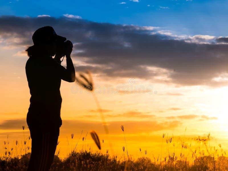 Sylwetka fotograf w trawy polu obraz stock