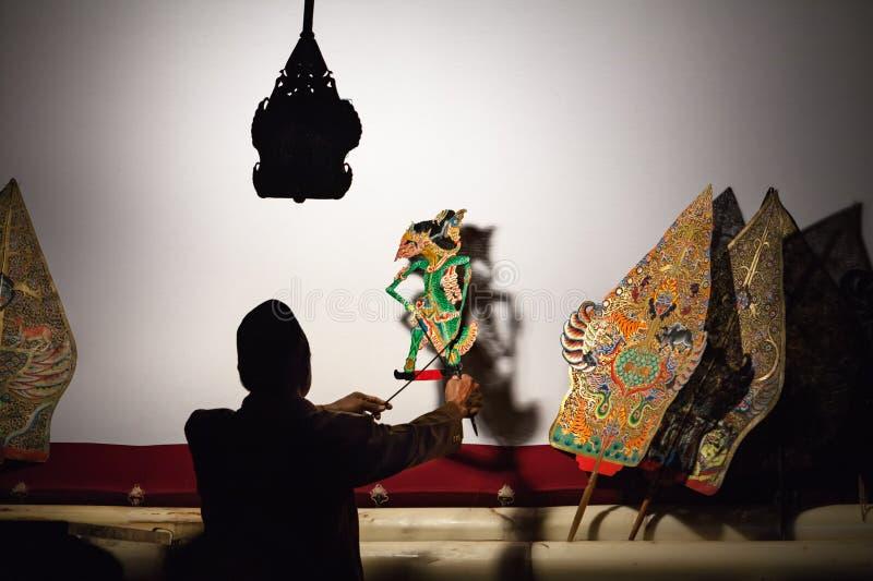 Sylwetka indonezyjski puppeteer z starymi javanese cienia kukłami obrazy royalty free