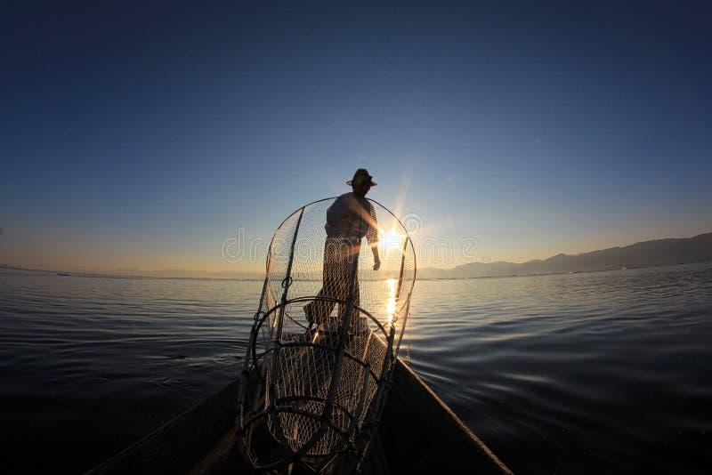 Sylwetka intha rybak przeciw zmierzchu niebu zdjęcia stock