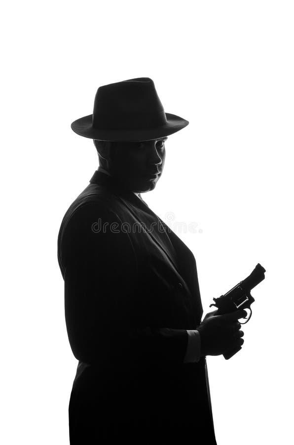 Sylwetka intymny detektyw z pistoletem w prawej ręce Agenta pobytu strona kamera i spojrzenia jak mafioso Al Capone Przestępcy sc fotografia stock
