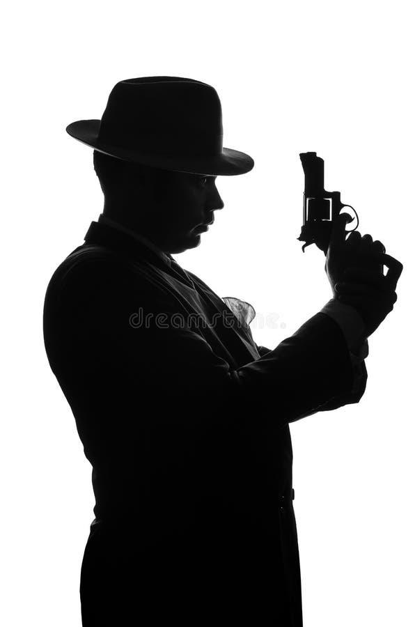 Sylwetka intymny detektyw z pistoletem w prawej ręce Agenta pobytu strona kamera i spojrzenia jak mafioso Al Capone Przestępcy sc zdjęcie stock