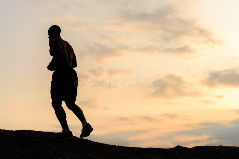 Sylwetka jogging na zmierzchu w górach amerykanin afrykańskiego pochodzenia atleta plenerowy szkolenie Sporta i sprawności fizycz obraz royalty free