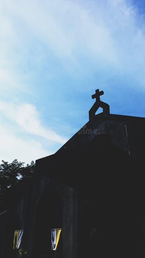 Sylwetka kościół przód z krzyżem przy wierzchołkiem z białymi i żółtymi flagami przy dnem przy St benedyktynki monasterem fotografia stock