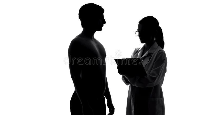 Sylwetka kobieta doktorski egzamininuje męski pacjent, opieka zdrowotna i medycyna, obrazy stock