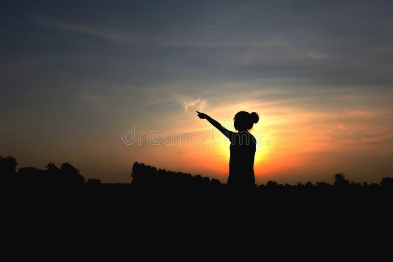 Sylwetka kobieta przy zmierzchem, Stoi posturę, blisko Ciemnawego zdjęcia stock