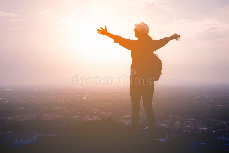 Sylwetka kobieta turysta rozprzestrzenia jego ręki szerokie jako wolność na krajobrazie lub zwycięzca obraz royalty free